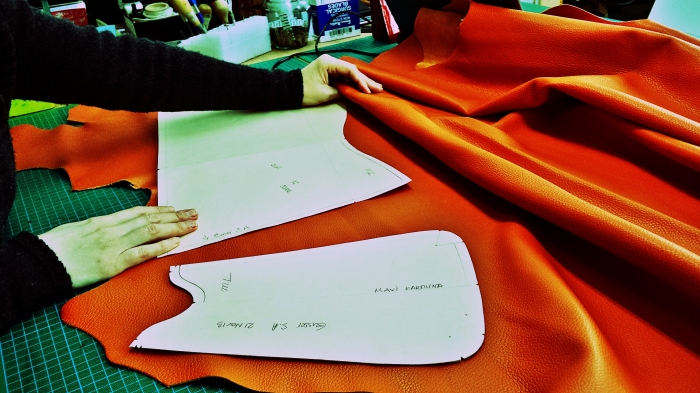 Aligning the patterns on the leather ready for cutting.