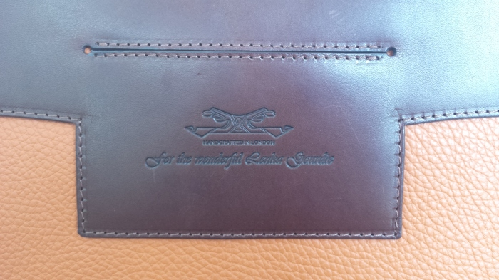 The embossed message attached onto the card pocket and stitched on to the bag.